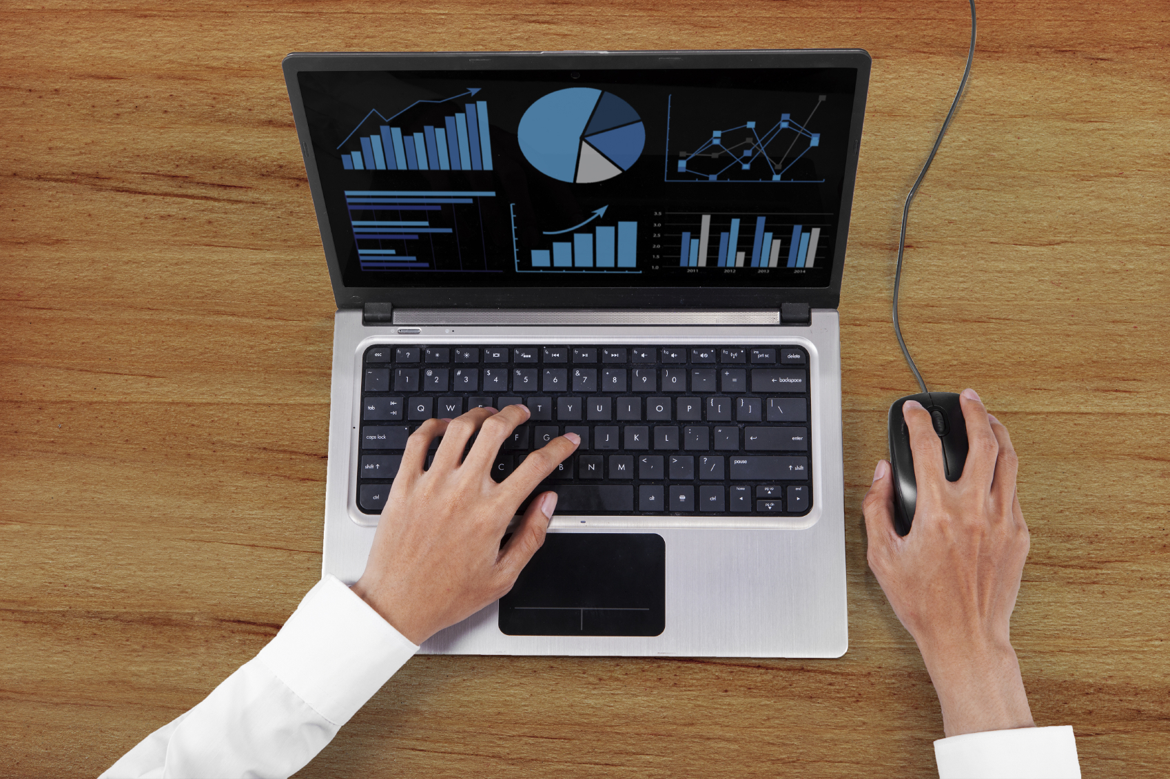 High angle view of businessman hands working with laptop computer and mouse