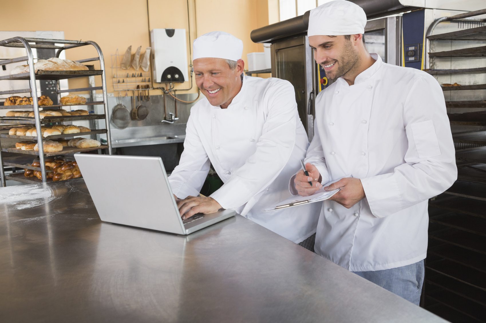 Smiling bakers working together on laptop_Medium